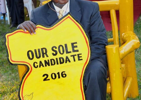 President-Museveni-on-chair-with-map-handed-to-him-by-Traders-at-a-rally-in-Kihiihi,-Kinkizi-West,-2nd-July-2014